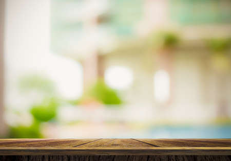 Wooden floor and blur outside house with green garden background