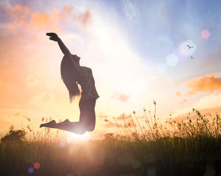 Wellbeing concept: Silhouette of happy woman jumping with her hands raised at orange autumn nature sunset background Stock Photo