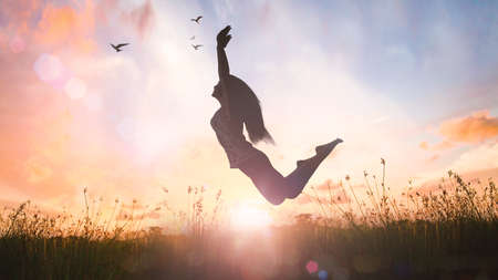 Wellbeing concept: Silhouette of happy woman jumping with her hands raised at orange autumn nature sunset background 免版税图像