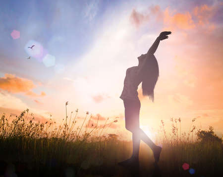 World mental health day concept: Silhouette of healthy woman raised hands for praise and worship God at autumn sunset meadow background Stock Photo