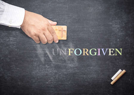 Forgiven concept: Human hand erased alphabet U, N from a chalkboard for changing to FORGIVEN