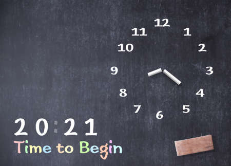 Concept for 2021 time to begin: Hand-drawing clock with text on grungy blackboard