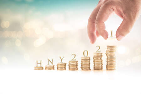 Human hand arrange HNY 2021 letter is mean Happy New Year 2021 on stack of coin