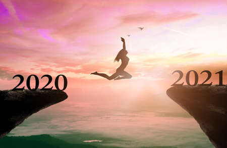 Success new year 2021 concept: Silhouette woman jump between 2020 and 2021 years with sunset background 免版税图像