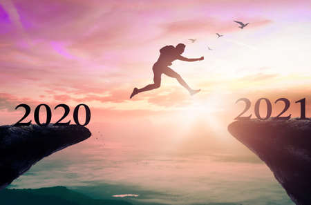 Success new year 2021 concept: Silhouette man jump between 2020 and 2021 years with sunset background
