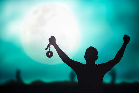 Motivate concept: Winner hand raised and holding gold medal reward against full moon on blue night sky background 免版税图像