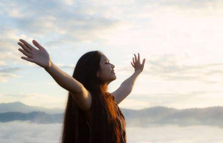 Worship God concept: Happy girl raised hand on blurred mountain sunrise background. Ai Yerweng, Bethong, Yala, Thailand, Asia Imagens