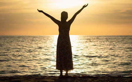 Worship God concept: Silhouette Asian woman raised hand on beach sunset background