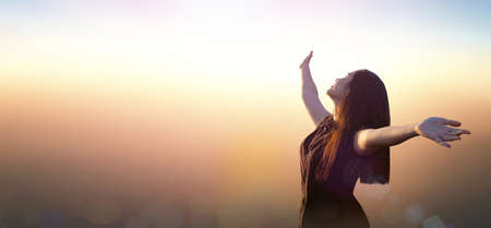 Worship God concept: Happy girl raised hand on blurred mountain sunrise background