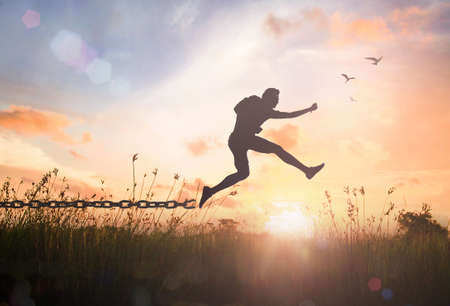 Freedom concept: Silhouette of a man jumping and broken chains at autumn sunset meadow background Standard-Bild