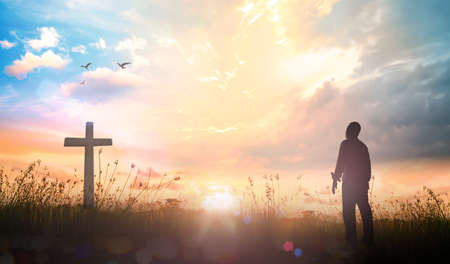 Praise and worship concept: Silhouette human standing and the cross on meadow sunset background