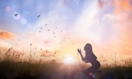 Worship God concept: Silhouette of prayer woman bow down and praying over autumn sunset background Standard-Bild