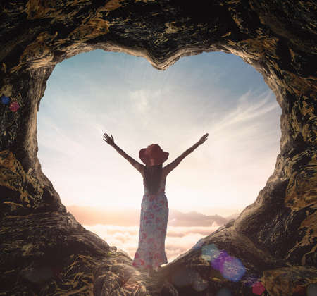 Worship God concept: Silhouette alone woman standing on cave of heart and sea of fog sunrise background