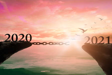 Success new year 2021 concept: Text 2020 and 2021 with bird flying and broken chains against mountain sunrise background Standard-Bild