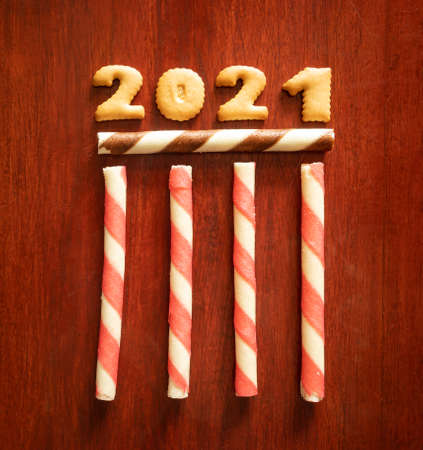 2021 text from cookies with candy on the wooden table background