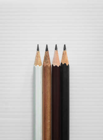 Difference concept: Four pencils, white brown dark brown and black, on white corrugated plastic board background