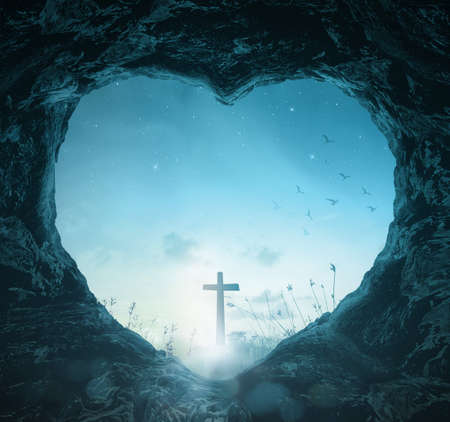 Crucifixion of Good Friday concept: Heart shape of empty tomb stone with silhouette cross over meadow night background