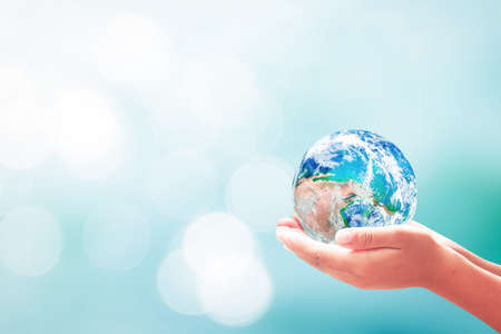 Sustainable development goals (SDGs) concept: Human hands holding earth global over blurred blue water background. Banque d'images