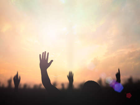 Worship God concept: Silhouette christian people hand rising over blurred cross on spiritual light background