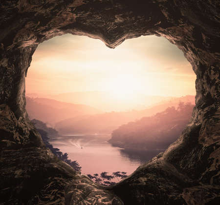 Heart shape of cave on river and mountains sunset background Banque d'images