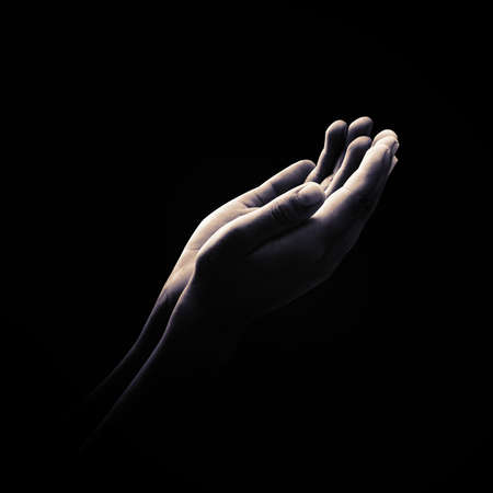 Ramadan kareem concept: Black and white muslim prayer open two empty hands with palms up on dark room background