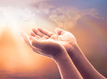 Faith God concept: Human open two empty hands with palms up over blurred world map of clouds with rainbow background