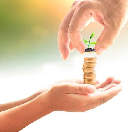 Father's day concept: Hand of father give one coin with small plant into stacks of golden coins in hands of son over blurred nature background