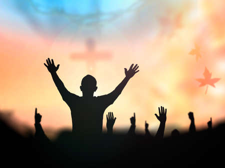 Praise and worship concept: Silhouette human raising hands to praying God on blurred cross with crown of thorn sunset background Banque d'images