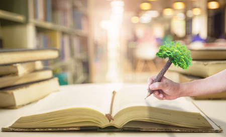 Teacher day concept: Student hand holding pencil of tree and writing on old book in blurred library background