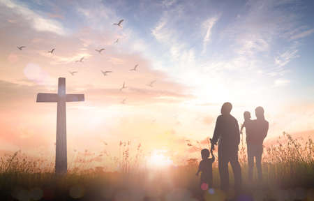 Easter Sunday concept: Silhouette family looking for the cross of Jesus Christ on autumn sunrise background