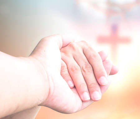 Jesus holding hand of someone for help over blurred the cross and crown of thorn sunset background Banque d'images