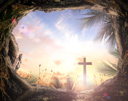 Palm Sunday concept: Silhouette cross and empty tombstone with palm leaves over meadow sunset background Banque d'images