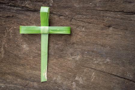 Palm Sunday concept: Cross shape of palm branch on an antique wood Standard-Bild