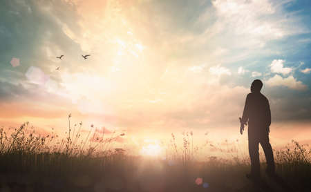 Silhouette humble man standing on sunlight with meadow autumn sunset