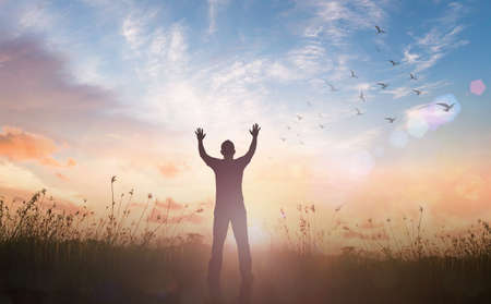Praise and worship God concept: Silhouette of healthy man raised hands at meadow sunset background Banque d'images