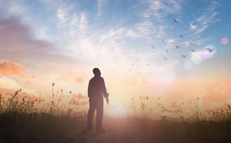 Praise and worship God concept: Silhouette of healthy man standing against meadow sunset background
