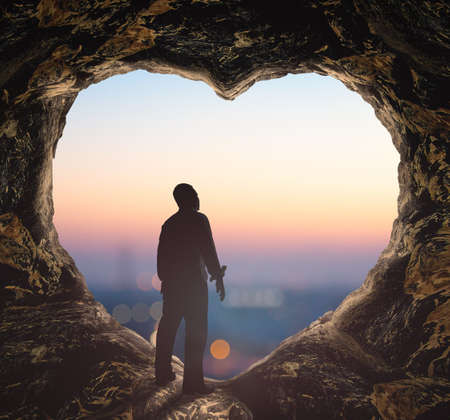 Worship God concept: Silhouette human standing on cave of heart against blurred city sunrise background Banque d'images