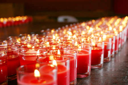 lighten: red burning candles in a temple