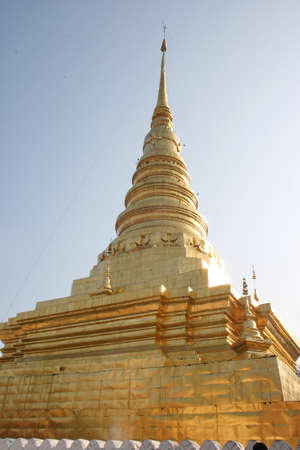 golden pagoda with blue sky in a temple, Thailand photo