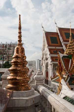 golden mosaic pagoda with blue sky in a temple, Thailand photo