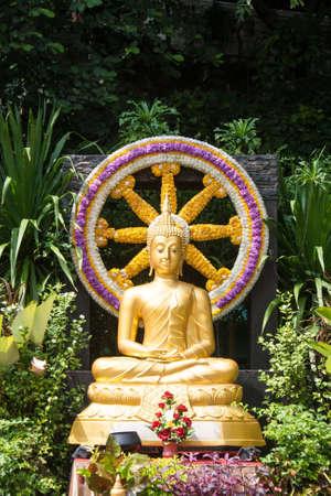 dhamma: statua d'oro del Buddha � seduto di fronte a Ruota del Dhamma