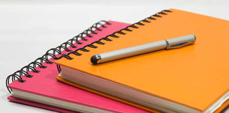 Close-up of pink orange note book and pen