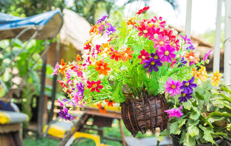 colorful Plastic flowers in wooden vase hang on a tree photo