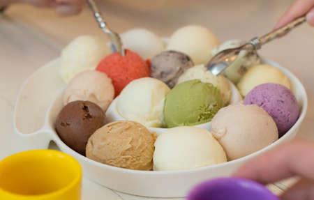 Mangiare vario gusto di gelato scoop in un piatto con il cucchiaio Archivio Fotografico - 21132701