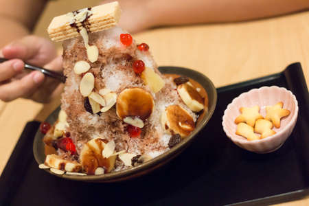 eatting banana shaved Ice with wafer, Snow cone dessert  and biskit Stock Photo