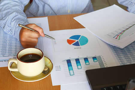 forcasting and analyzing sales charts and graphs report with coffee cup photo