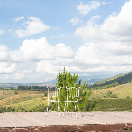 balcony view: a beautiful white two chairs in balcony view of green mountain with love
