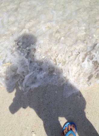 topdown: shadow of traveler with sea wave bubbles foam on the beach, top-down view
