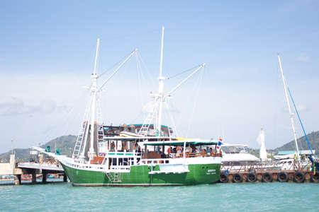mujer mirando el horizonte: blanco barco de vela navegando en el mar azul