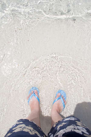 topdown: sea wave bubbles comes to feet walking on the beach, top-down view Stock Photo